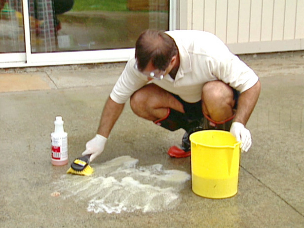 Man demonstrating how to get stains out of concrete