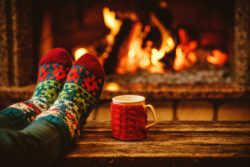 hygge feet in socks in front of fireplace