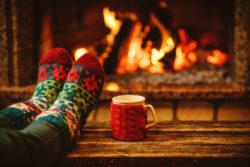 hygge feet in socks in front of fireplace